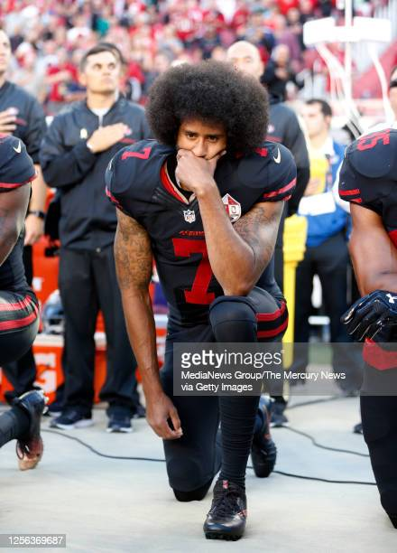 San Francisco 49ers quarterback Colin Kaepernick covers is mouth as he kneels during the national anthem before their NFL game against Arizona...