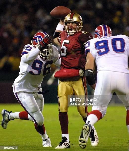 San Francisco 49ers' quarterback Jeff Garcia hurries a pass as Buffalo Bills' defensive tackle Erik Flowers and defensive tackle Phil Hansen pressure...