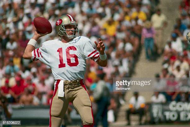 San Francisco 49ers quarterback Joe Montana is shown with his arm cocked back, ready to throw the football during a game.