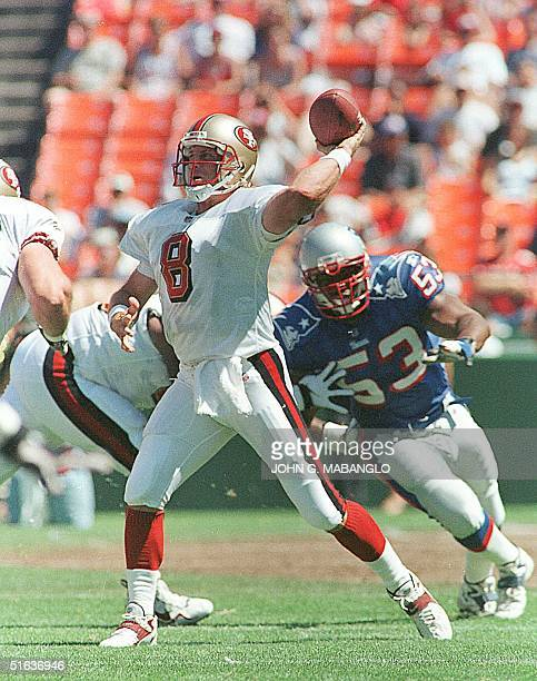 San Francisco 49ers quarterback Steve Young drops back to pass as New England Patriots linebacker Chris Slade closes in 02 August in San Francisco CA...