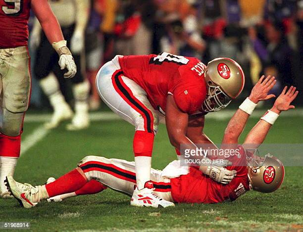 San Francisco 49ers quarterback Steve Young is congratulated by tackle Steve Wallace as he signals his fifth touchdown pass of the game against the...