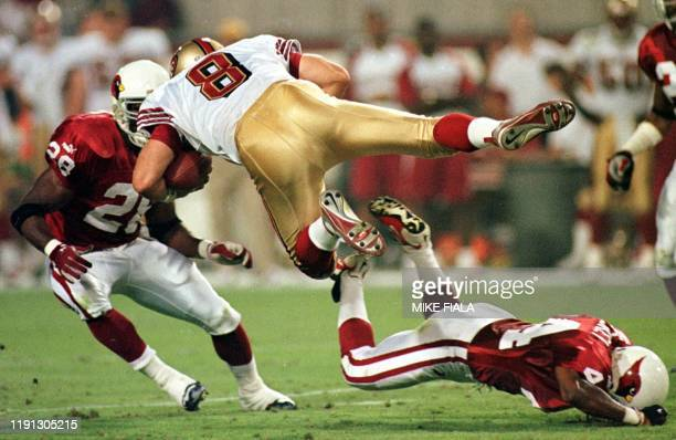 San Francisco 49ers quarterback Steve Young is sent airborne by Arizona Cardinals cornerback JJ McCleskey as Cardinals safety Tommy Bennett moves in...