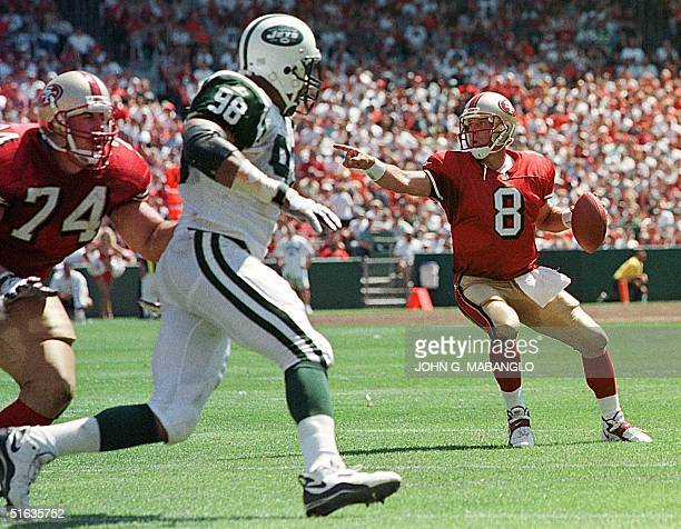 San Francisco 49ers quarterback Steve Young looks for a receiver as 49ers Dave Fiore defends New York Jets Anthony Pleasant 06 September in San...