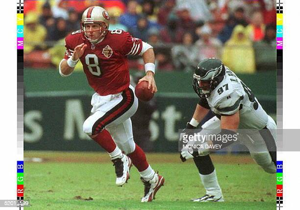 San Francisco 49ers quarterback Steve Young rushes for yardage while eluding the tackle from Philadelphia Eagles defensive tackle Rhett Hall during...
