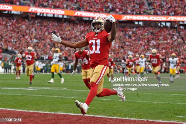 San Francisco 49ers' Raheem Mostert scores a touchdown in front of Green Bay Packers' Jaire Alexander in the first quarter of their NFC Championship...