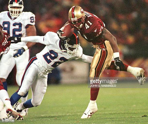 San Francisco 49ers runningback Terry Kirby breaks a tackle from New York Giants Phillippi Sparks 30 November in San Francisco CA The 49ers defeated...