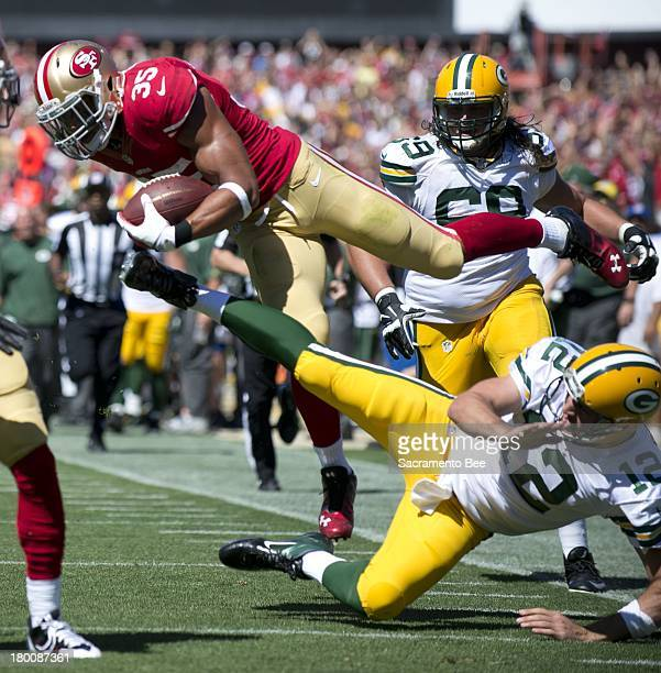 San Francisco 49ers safety Eric Reid is stopped near the end zone by Green Bay Packers quarterback Aaron Rodgers after Reid intercepted a pass at...