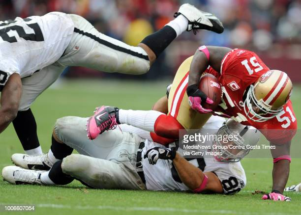 San Francisco 49ers Takeo Spikes #51 falls to the ground on top of Oakland Raiders Zach Miller #80 after intercepting a pass in the fourth quarter of...
