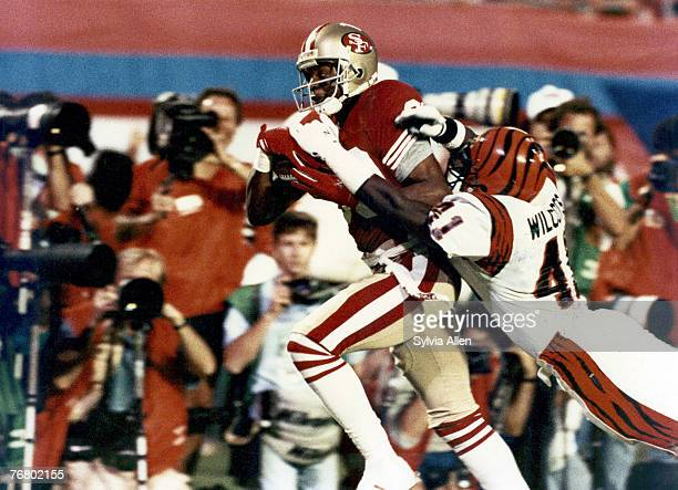 San Francisco 49ers wide receiver Jerry Rice runs with the football after making a catch and drags Bengals defensive back Solomon Wilcots along the...