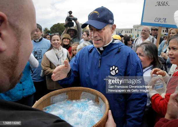 San Francisco Archbishop Cordileone blesses a basket of rosaries before the hundreds gathered to show support for him during a picnic at the Sue...