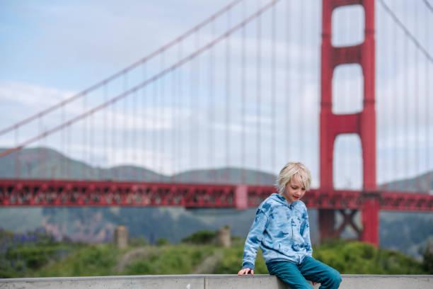 USA, CA, San Francisco, Boy sitting on wall near Golden Gate Bridge