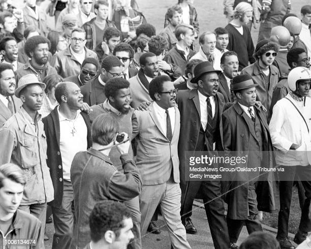 Arminarm African American community leaders head a march across SF State caompus to a protest rally In the forefront are Dr Cecil Williams Dr...