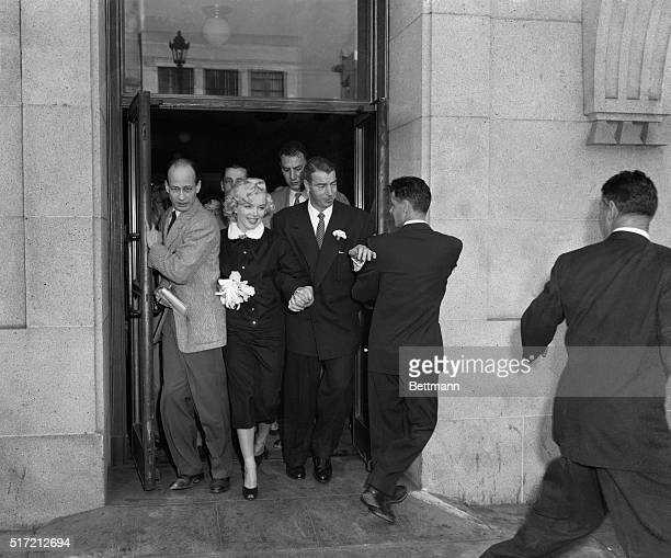 """San Francisco, CA: """"Mr and Mrs."""" Film star Marilyn Monroe and former Yankee great Joe Di Maggio press through a crowd of newsmen after their marriage..."""