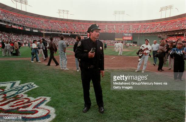 San Francisco, CA October 17, 1989: San Francisco police officer stands near home plate at Candlestick Park just after the Loma Prieta earthquake...