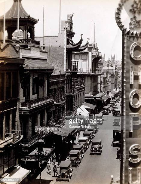Overhead view of a street in the Chinatown section of San Francisco seen from a building window The street is lined with signs advertising Chop Suey...