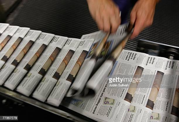 San Francisco Chronicle journeyman pressman Ray Lussier pulls two freshly printed copies of the Chronicle at one of the Chronicle's printing...