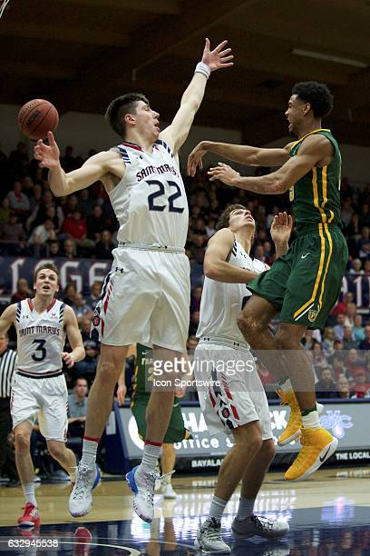 San Francisco Dons center Jimbo Lull passes midair under pressure from St Mary's Gaels forward Dane Pineau during the Gaels' 6646 victory against the...