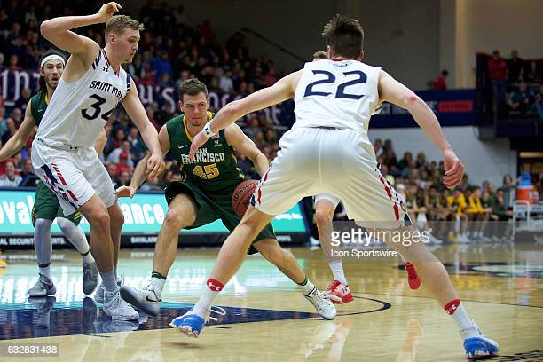 San Francisco Dons guard Mladen Djordjevic dribbles into St Mary's Gaels center Jock Landale and St Mary's Gaels forward Dane Pineau during the first...
