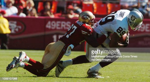 San Francisco Forty Niners Walt Harris wraps up Oakland Raiders Ronald Curry in the 3rd quarter of their game at Monster Park in San Francisco Sunday...