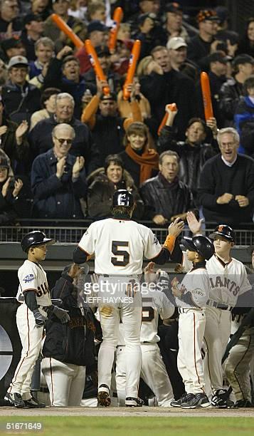 San Francisco Giant Tsuyoshi Shinjo is greeted by his teammates after scoring a run on a Rich Aurilia threerun home run against he Anaheim Angels in...