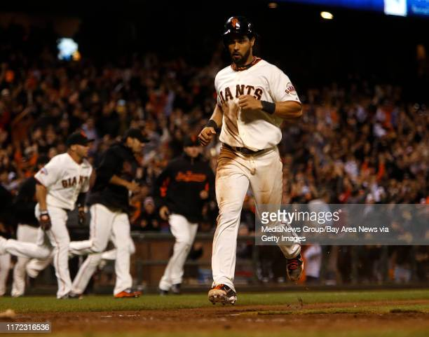 San Francisco Giants' Angel Pagan scores the game winning run off of a single by San Francisco Giants' Brandon Belt against the Colorado Rockies in...
