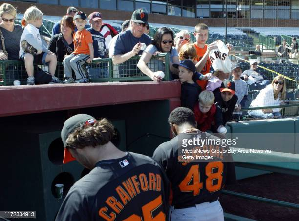 San Francisco Giants' Brandon Crawford and Pablo Sandoval sign autographs during a spring training workout at Scottsdale Stadium in Scottsdale Ariz...
