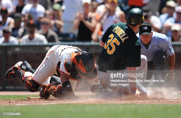 San Francisco Giants catcher Bengie Molina, #1, tags out Oakland Athletics Landon Powell, #35, as he attempts to score at home plate in the fourth...