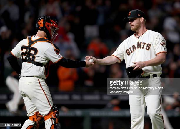 San Francisco Giants catcher Buster Posey hands relief pitcher Will Smith the ball after he struck out Los Angeles Dodgers left fielder Joc Pederson...