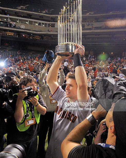 San Francisco Giants catcher Buster Posey hoists the Commissioner's Trophy after the Giants beat the Texas Rangers to win the World Series at Rangers...