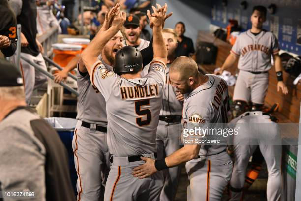 San Francisco Giants catcher Nick Hundley is greeted by San Francisco Giants third baseman Evan Longoria and San Francisco Giants outfielder Hunter...