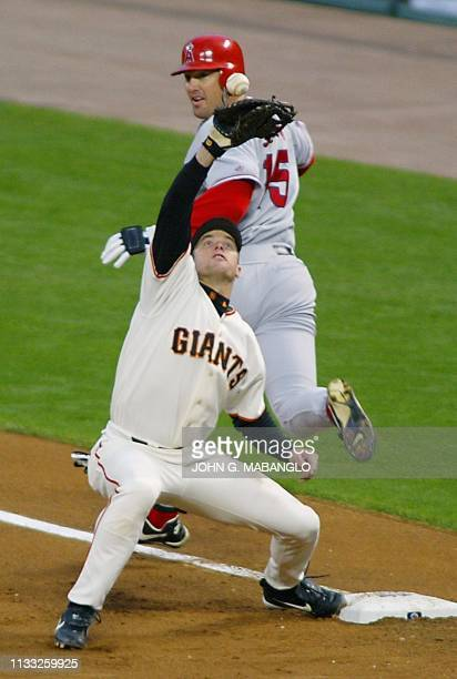 San Francisco Giants' first baseman JT Snow loses control of the ball thrown from third baseman David Bell as Anaheim Angels' Tim Salmon is safe at...
