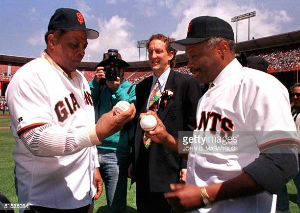 San Francisco Giants Hall of Famer Willie Mays shows San Francisco Mayor Willie Brown how to hold a baseball for pitching before they are to throw...