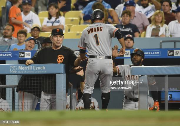 San Francisco Giants infielder JaeGyun Hwang is congratulated by manager Bruce Bochy after sliding in safely at home for a run in the seventh inning...