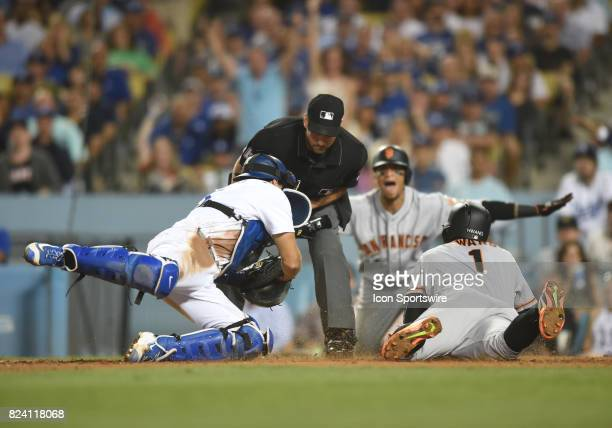 San Francisco Giants infielder JaeGyun Hwang slides in safely at home for a run against Los Angeles Dodgers catcher Austin Barnes in the seventh...