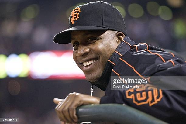 San Francisco Giants left fielder Barry Bonds watches the game from the Giants dugout after a press conference earlier in the day announcing the...
