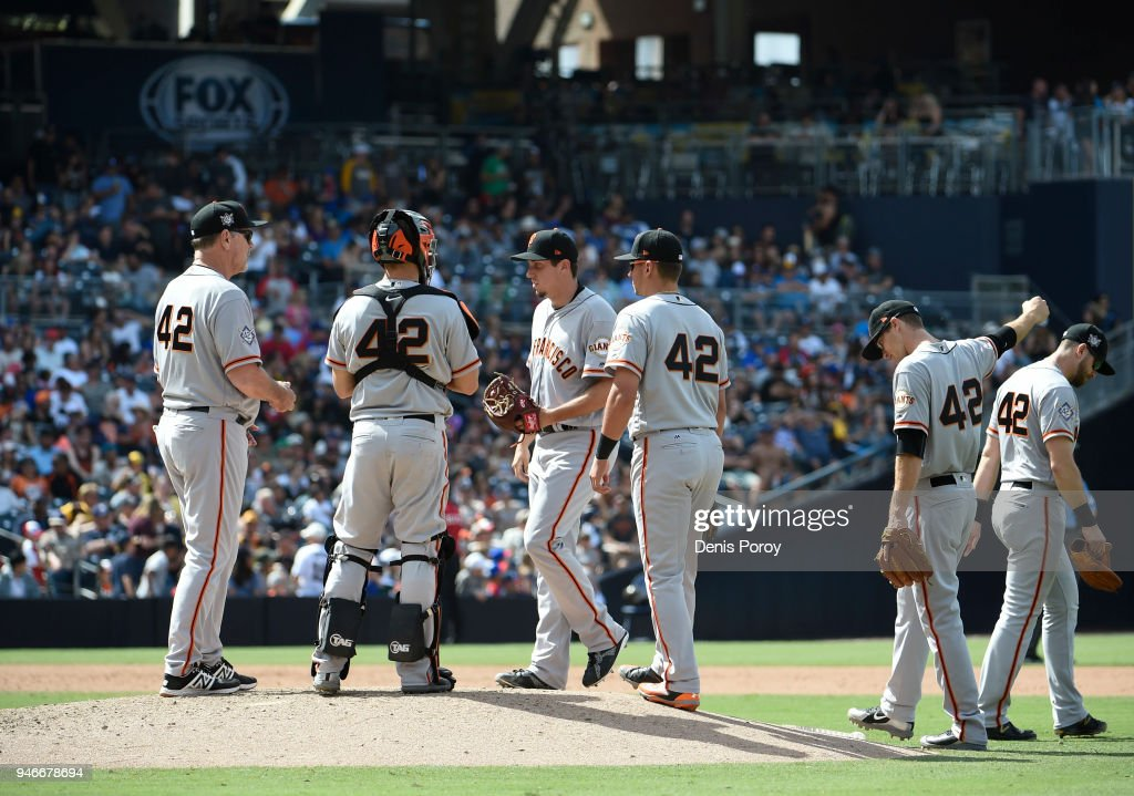 San Francisco Giants manager Bruce Bochy, (L) waits as Derek Law #64, (C) comes into the game during the sixth inning of a baseball game against the San Diego Padres at PETCO Park on April 15, 2018 in San Diego, California. All players are wearing #42 in honor of Jackie Robinson Day.