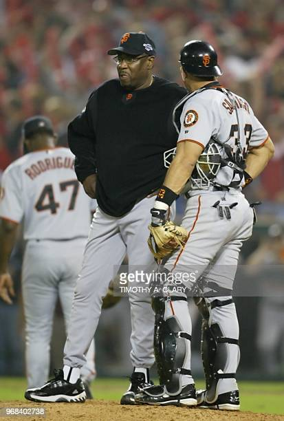 San Francisco Giants' manager Dusty Baker talks with catcher Benito Santiago after sending relief pitcher Felix Rodriguez off the mound in the eighth...