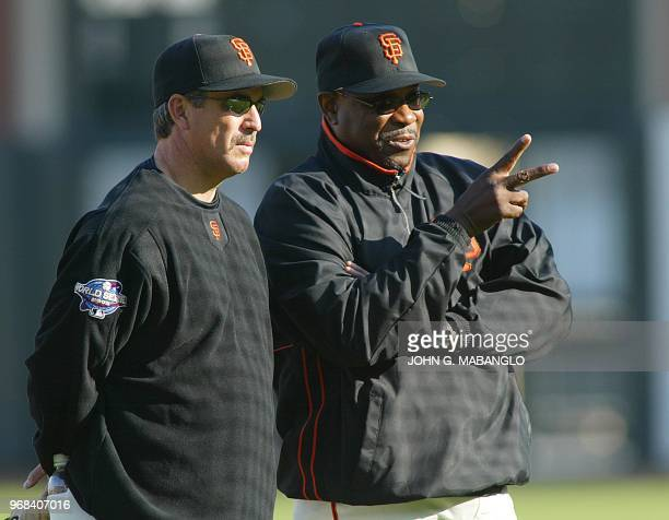 San Francisco Giants' manager Dusty Baker talks with coach Ron Wotus during practice at Pacific Bell Park 21 October 2002 in San Francisco The Giants...
