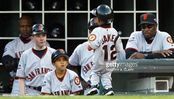 San Francisco Giants manager Dusty Baker watches his son Darren carry a bat along with Barry Bonds and some of the Giants bat boys during Game 6 of...