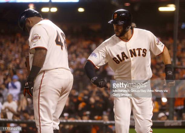 San Francisco Giants' Michael Morse taps San Francisco Giants' Pablo Sandoval on the backside after Morse scored in the sixth inning of Game 3 of...