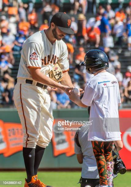 San Francisco Giants Pitcher Andrew Suarez signs a ball for a young fan before the game between the Los Angeles Dodgers and the San Francisco Giants...