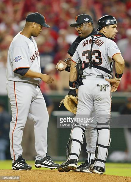 San Francisco Giants' pitcher Livan Hernandez is sent off the pitcher's mound by manager Dusty Baker as catcher Benito Santiago waits for relief...
