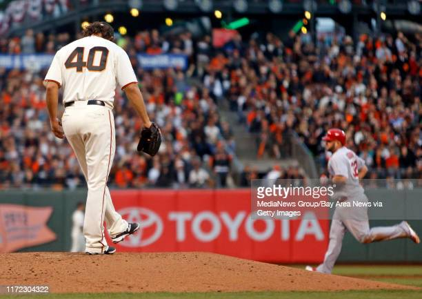 San Francisco Giants pitcher Madison Bumgarner left, stands on the pitchers mound as St. Louis Cardinals' Matt Adams rounds the bases after hitting a...