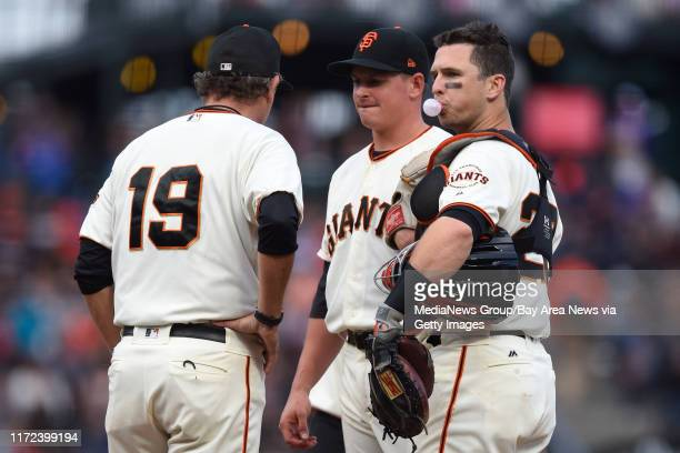 San Francisco Giants pitching coach Dave Righetti speaks to San Francisco Giants pitcher Kyle Crick as catcher Buster Posey blows a bubble in the...