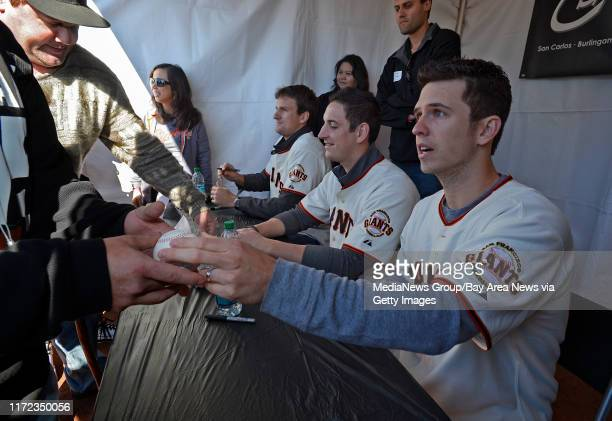 San Francisco Giants players Dan Otero from left Eric Surkamp and Buster Posey sign autographs for fans during the 2013 Giants Fan Fest at ATT Park...