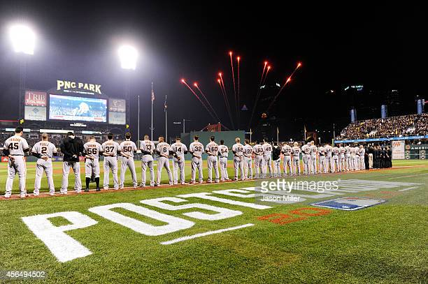 San Francisco Giants players stand at attention during the national anthem prior to their National League Wild Card game against the Pittsburgh...