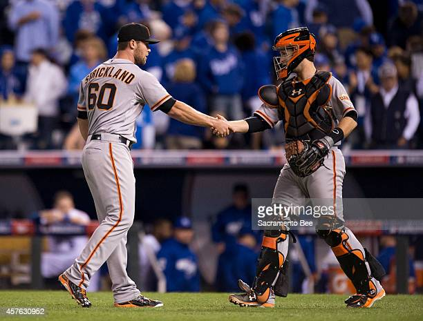 San Francisco Giants relief pitcher Hunter Strickland and catcher Buster Posey congratulate each other after a 71 win against the Kansas City Royals...