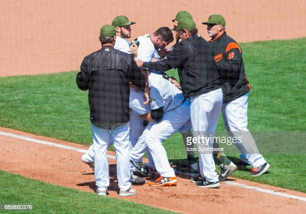 San Francisco Giants relief pitcher Hunter Strickland is restrained after brawl took place during the regular season MLB game between the San...