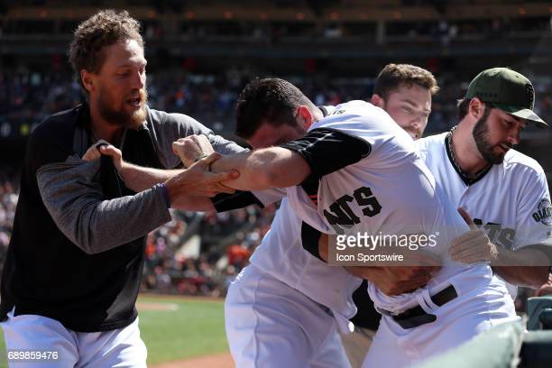 San Francisco Giants relief pitcher Hunter Strickland needs to be physically restrained to be removed from the field by teammates Hunter Pence and...