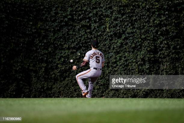 San Francisco Giants right fielder Mike Yastrzemski misses a ball hit by the Chicago Cubs' Kyle Schwarber during the seventh inning at Wrigley Field...